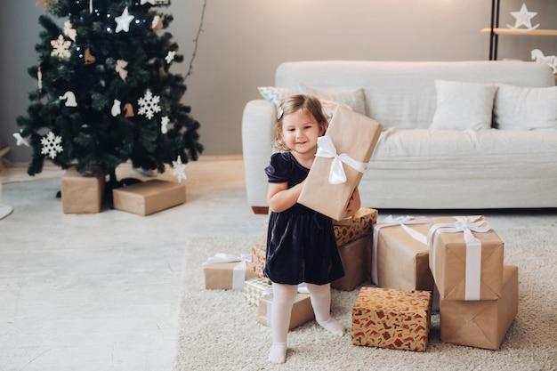 Ein schönes kaukasisches mädchen mit kurzen blonden welligen haaren in einem niedlichen schwarzen kleid sitzt neben weihnachtsgeschenken in einem großen hellen raum des hauses