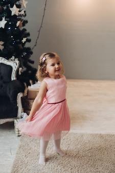 Ein schönes kaukasisches mädchen mit kurzen hellen welligen haaren in einem niedlichen rosa kleid freut sich nahe dem weihnachtsbaum in einem großen hellen raum des hauses