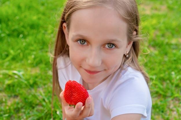 Ein schönes kind mit grünen augen hält erdbeeren in den händen und lächelt. sommer, lifestyle-konzept der kindheit.