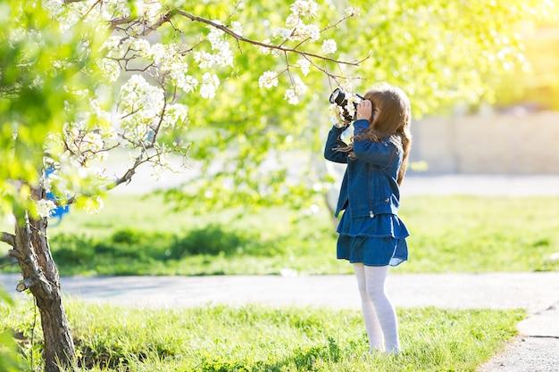 Ein schönes kleines mädchen hält eine kamera in ihren händen.