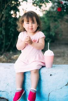 Ein schönes kleines mädchen in einem rosa kleid vor dem hintergrund der pflanzen sitzt neben einem niedlichen cocktailglas