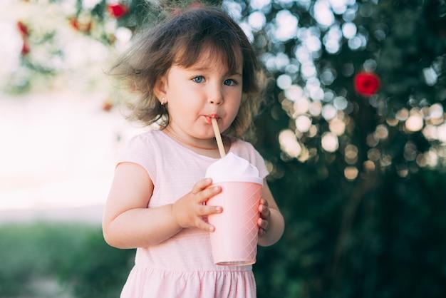 Ein schönes kleines mädchen in einem rosa kleid vor dem hintergrund der pflanzen trinkt ein getränk aus einem niedlichen cocktailglas