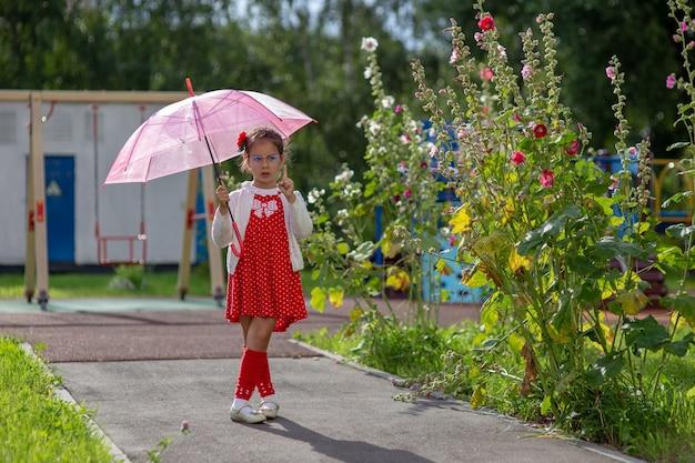 Ein schönes kleines mädchen in einem roten kleid und einer weißen bluse mit einem rosa regenschirm steht im sommertag. horizontal.