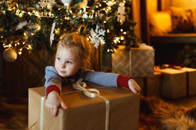 Ein schönes kleines mädchen umarmt einen kasten mit einem weihnachtsgeschenk vor einem verzierten weihnachtsbaum.