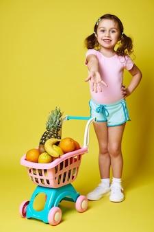 Ein schönes kleines mädchen zeigt ihre hand und zeigt einen einkaufswagen voller köstlicher früchte. isoliert auf gelber wand, kopierraum
