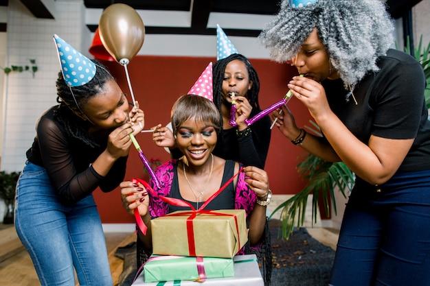 Ein schönes lächelndes afrikanisches mädchen öffnet ein geschenk auf ihrer geburtstagsfeier