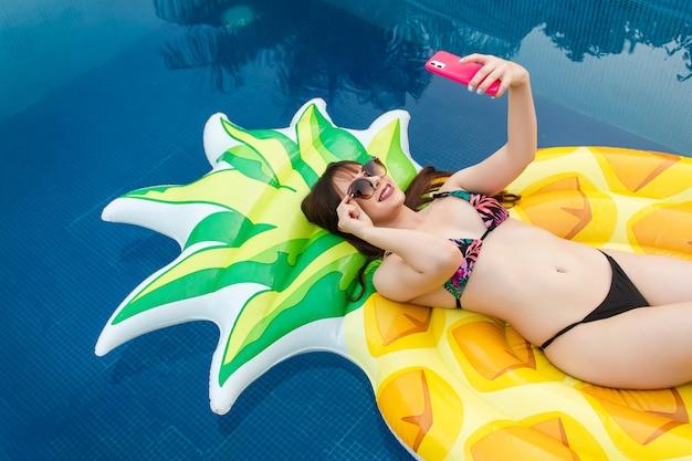 Ein schönes lächelndes mädchen, das ein selfie mit ihrer sonnenbrille auf ihrem schwimmer im pool hält.