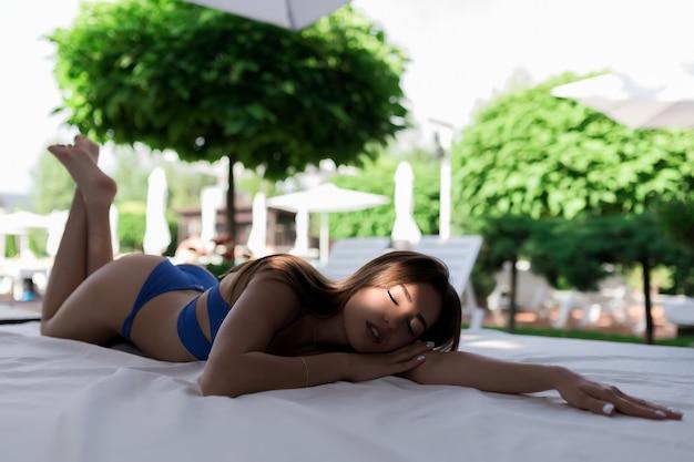 Ein schönes lächelndes mädchen in einem blauen badeanzug liegt an einem sommertag im schatten