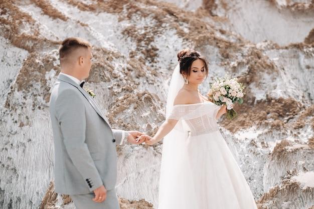 Ein schönes liebespaar posiert in einem weißen salzberg. eine junge frau in einem stylischen hochzeitskleid und ein schöner stylischer mann in einem grauen anzug. das konzept des hochzeitstages.