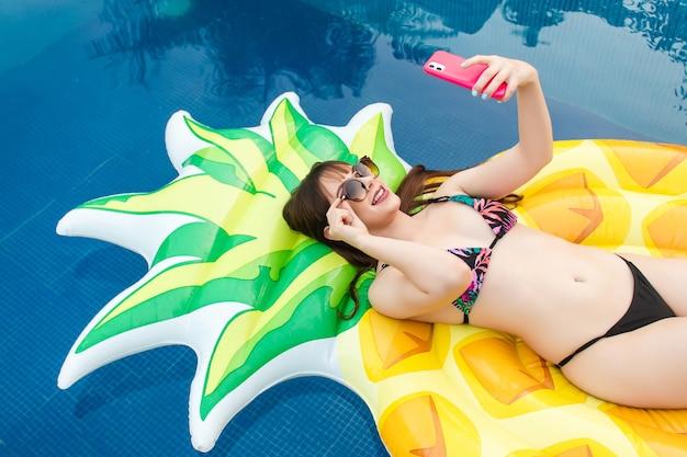 Ein schönes mädchen, das ein selfie mit ihrer sonnenbrille auf ihrem schwimmer im pool hält.