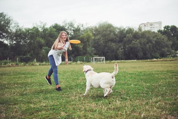 Ein schönes mädchen, das mit ihrem geliebten hund im park spielt.