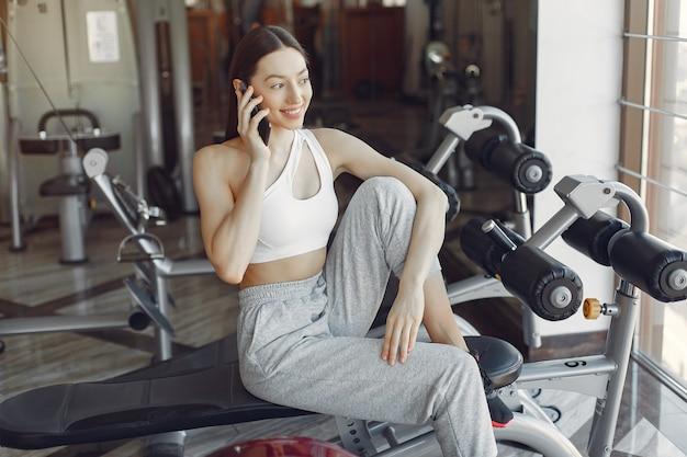 Ein schönes mädchen, das mit telefon in einem fitnessstudio sitzt