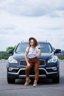 Ein schönes mädchen europäischen aussehens mit brille und braunem hut steht in der nähe eines schwarzen autos. foto in der nähe des autos.