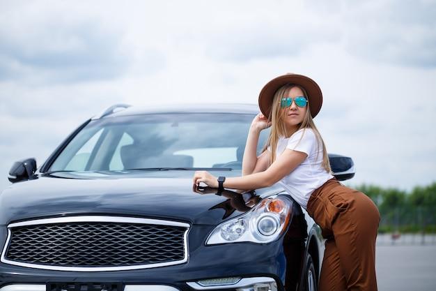 Ein schönes mädchen europäischen aussehens mit brille und braunem hut steht in der nähe eines schwarzen autos. fotoshooting in der nähe des autos.