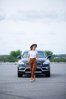 Ein schönes mädchen europäischen aussehens mit brille und braunem hut steht in der nähe eines schwarzen autos. junge frau mit auto auf dem parkplatz