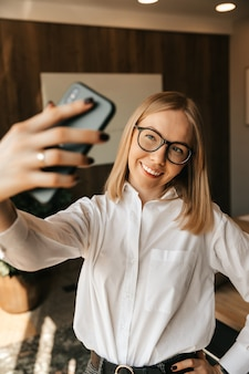 Ein schönes mädchen im büro macht ein selfie am telefon, ein foto auf einem smartphone bei der arbeit.