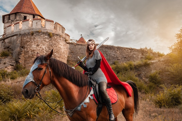 Ein schönes mädchen im kostüm der kriegerkönigin. eine frau zu pferd mit einem schwert in der hand.