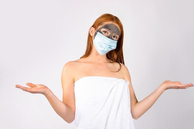 Ein schönes mädchen im salon mit einer kosmetischen maske im gesicht und wegen einer pandemie muss eine medizinische maske aufsetzen. hochwertiges foto