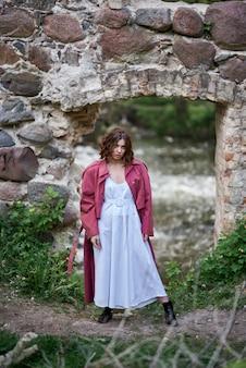 Ein schönes mädchen in einem kleid am ufer des flusses in der nähe der ruinen einer alten burg