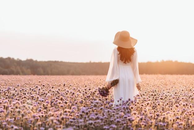 Ein schönes mädchen in einem lavendelfeld. eine schöne frau im stil der provence in einem weißen kleid mit einem blumenstrauß in den händen.