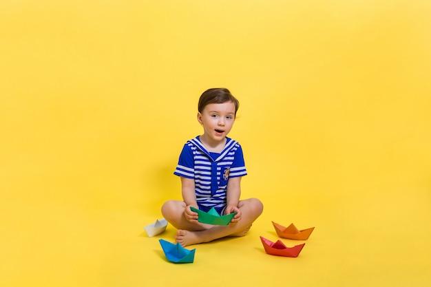 Ein schönes mädchen in einem matrosenkostüm spricht und hält ein grünes papierboot in den händen. freier platz auf einem gelben platz. papierorigami.