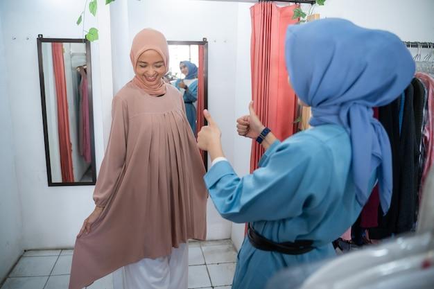 Ein schönes mädchen in einem schleier, das in einer umkleidekabine vor dem spiegel kleidung anprobiert, und ihre freundin...