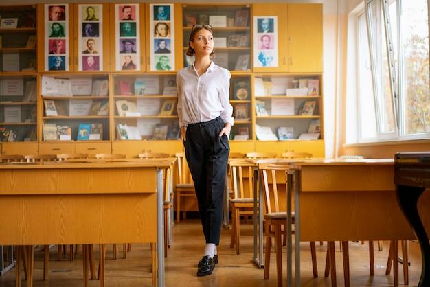 Ein schönes mädchen in einem weißen hemd steht im klassenzimmer zwischen den schreibtischen