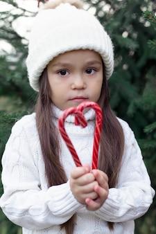 Ein schönes mädchen in einem weißen hut, ein blondes mädchen und in einem roten pullover lächelt im winter draußen