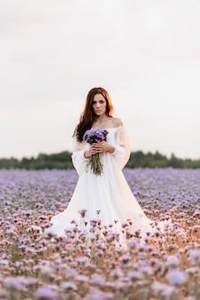 Ein schönes mädchen in einem weißen kleid in einem blühenden feld der provence in einer romantischen atmosphäre mit einem blumenstrauß in den händen