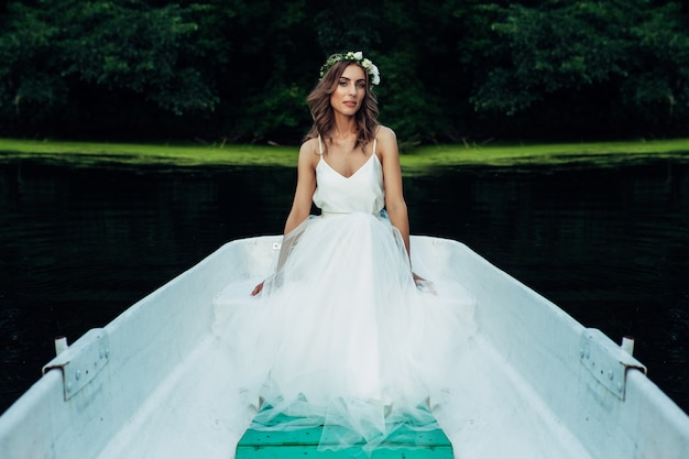 Ein schönes mädchen in einem weißen kleid und einem blumenkranz sitzt in einem boot auf dem fluss