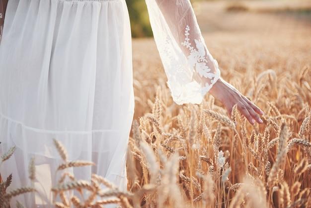 Ein schönes mädchen in einem weißen kleid verbringt ihre hand mit goldenen weizenspitzen.
