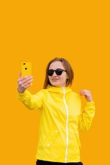 Ein schönes mädchen in einer gelben jacke macht ein selfie auf orangem hintergrund