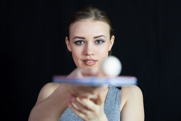 Ein schönes mädchen in einer sportklage rollt einen ball auf tennisschläger.