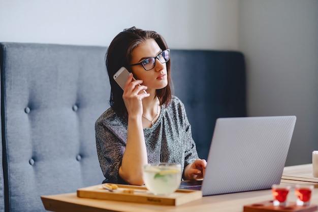 Ein schönes mädchen in gläsern spricht telefonisch für einen laptop in einem café