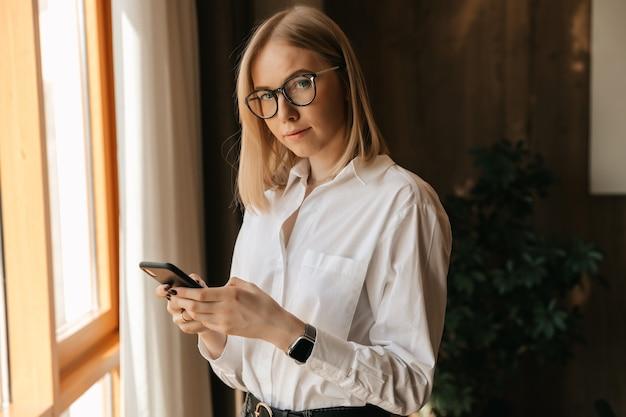 Ein schönes mädchen in gläsern steht am fenster im büro in ihren händen mit einem telefon, das text tippt.