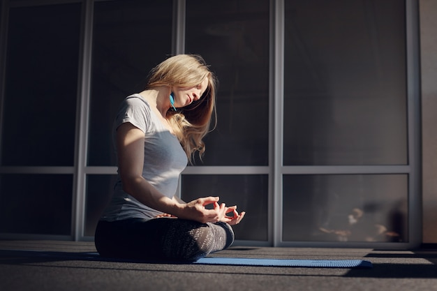 Ein schönes mädchen in sportkleidung meditiert während des yoga-unterrichts. die blondine sitzt in der lotus-position, entspannt sich und setzt ihr gesicht der sonne aus. das konzept eines gesunden lebensstils. seitenansicht