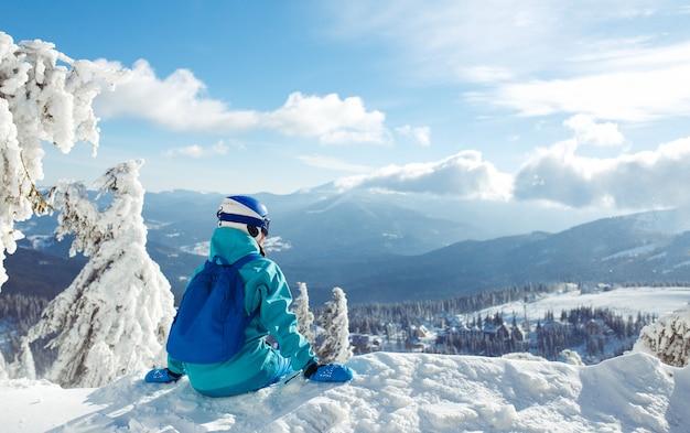 Ein schönes mädchen in winterkleidung, einem blauen helm und einer grünen jacke hat eine tolle zeit in den bergen.
