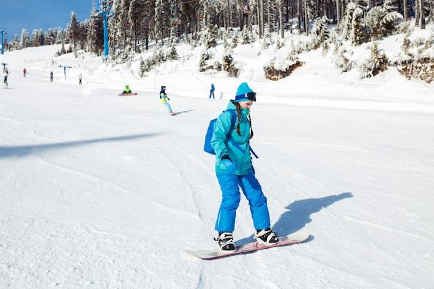Ein schönes mädchen in winterkleidung reitet ein snowboard.
