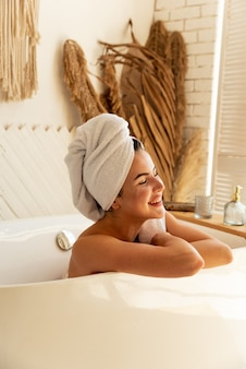 Ein schönes mädchen liegt im badezimmer. sie genießt und kümmert sich um sich selbst, indem sie badeprozeduren macht
