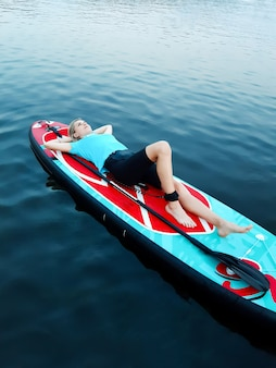Ein schönes mädchen liegt und ruht auf einem schwimmbrett und hält ihre hände hinter dem kopf vor dem hintergrund von ruhigem wasser