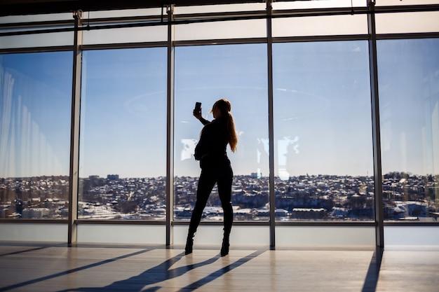 Ein schönes mädchen macht ein selfie auf ihrem handy vor dem hintergrund von panoramafenstern in einem wolkenkratzer