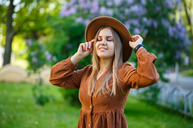 Ein schönes mädchen mit blonden haaren hält einen hut in den händen und steht mit geschlossenen augen in der nähe eines fliederbuschs. junge frau in einem garten mit blühenden bäumen