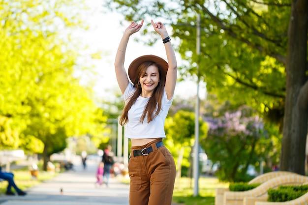 Ein schönes mädchen mit braunem hut und weißem t-shirt geht an einem warmen sonnigen tag auf die straße. schöne junge frau mit hut mit einem lächeln im gesicht