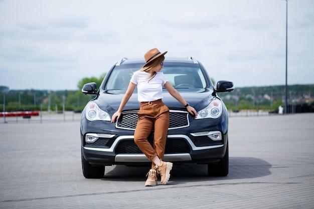Ein schönes mädchen mit brille und braunem hut steht in der nähe eines schwarzen autos. junge frau mit auto auf dem parkplatz