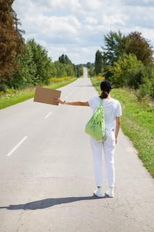 Ein schönes mädchen mit einem rucksack auf der schulter steht auf der straße, bremst das auto, per anhalter, abenteuer, tourismus, allein.