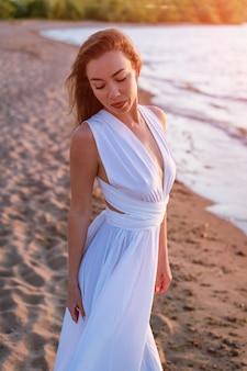 Ein schönes mädchen mit kaukasischem aussehen steht allein in einem langen weißen kleid an der küste im w...