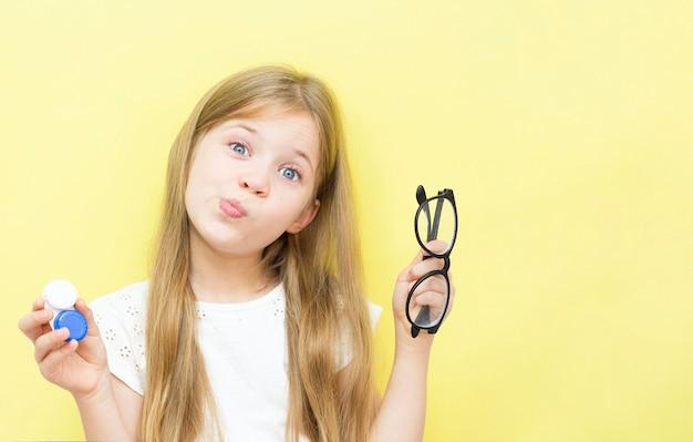 Ein schönes mädchen mit langen haaren hält einen behälter mit linsen und brille in den händen. das konzept der sehprobleme bei kindern. gelber hintergrund.