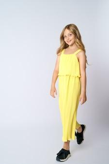 Ein schönes mädchen mit langen haaren in den gelben posen auf einem weißen hintergrund.