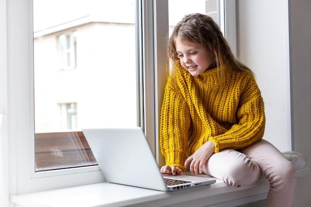 Ein schönes mädchen mit laptop zu hause am fenster schaut auf den bildschirm und lächelt