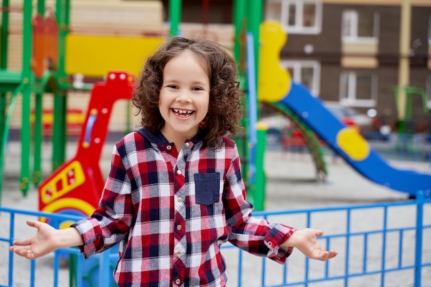 Ein schönes mädchen mit lockigen haaren in einem karierten hemd auf dem spielplatz lacht und streckt die hände zur seite